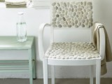 a white chair with a back and seat covered with pebbles is a great furniture piece for a beach home