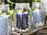 large jars with purple and lilac candles plus some white pebbles inside are great for indoor and outdoor decor
