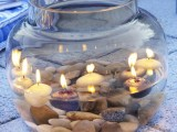 a large jar with pebbles and water plus floating candles is a cool centerpiece or relaxing decoration