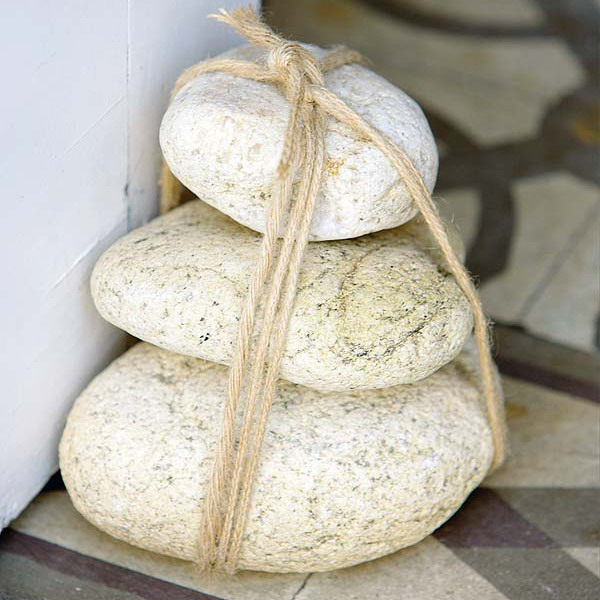 a doorstop made of a bunch of large pebbles with twine is a cool idea for a coastal home