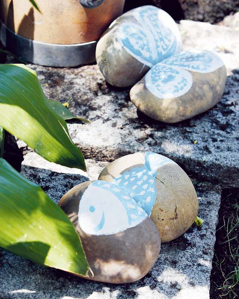 large pebbles with butterflies and fish painted on them are easy and cute garden decorations