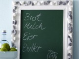 a chalkboard with a frame covered with pebbles is a cool beach or coastal home decor idea