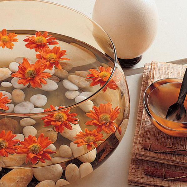 an aquarium with pebbles and bright blooms is a simple modern home decoration
