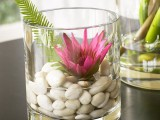 a glass with pebbles and water plus a leaf and a bold bloom is a beautiful arrangement for home decor