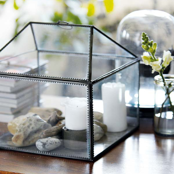 a terrarium with pebbles, driftwood and candles inside is a cool home decoration and can be made fast