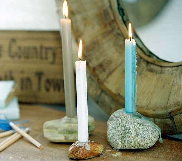large pebbles with holes drilled inside as simple and natural candle holders and candles inserted