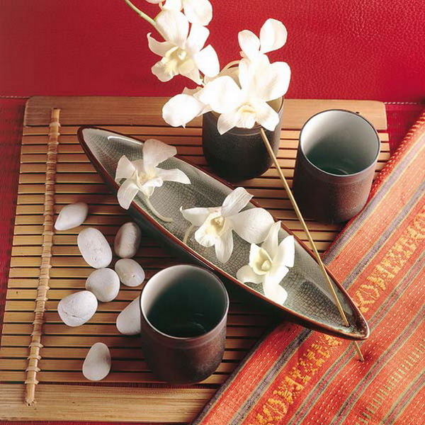 a beautiful zen arrangement with a bamboo mat, pebbles, cups, a bowl with blooms