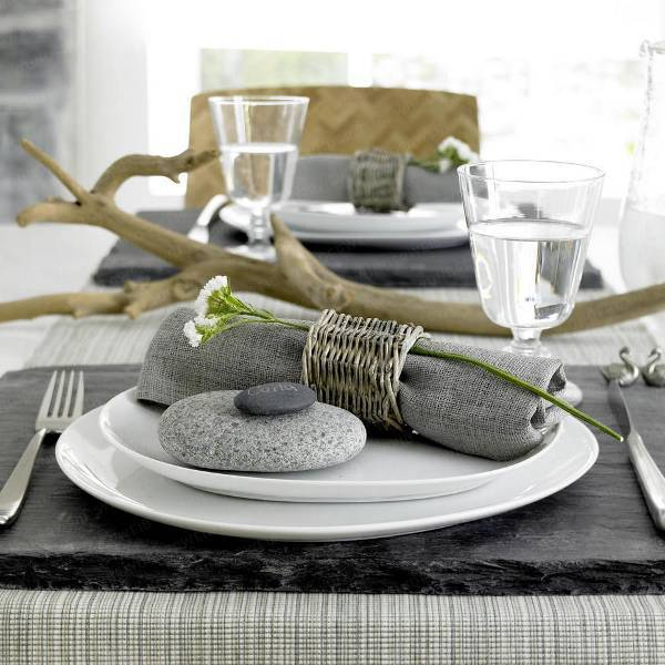 a natural coastal setting with a grey napkin with a wicker napkin ring, some pebbles and driftwood as a centerpiece