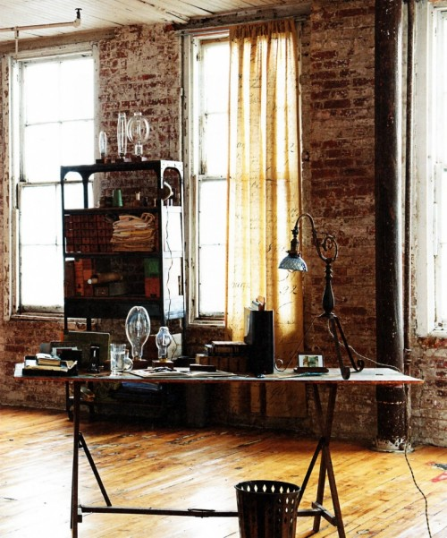 Bare brick wall, natural wood floors, and a vintage desk make this space an amazing working area