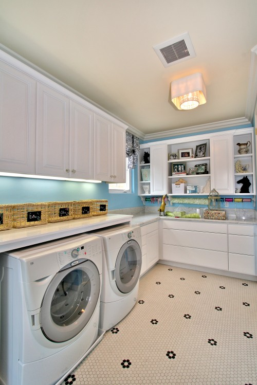 This spacious laundry room feature lots of white cabinets for storage and a nice light blue wall.
