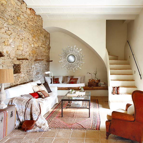 a living room with a bench under the stairs, spruce it up with pillows and blankets