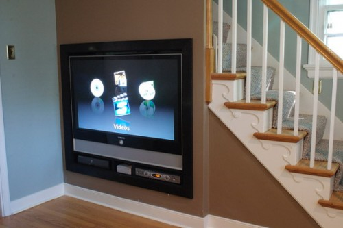 under the stairs space taken by a built-in TV is a great idea to use the awkward space in your home