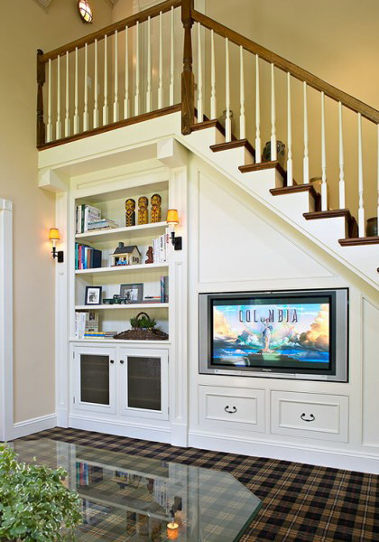 a staircase with bookshelves and a TV integrated and some storage drawers saves a lot of storage space
