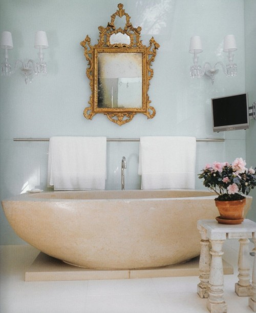 a refined bathroom with an oval stone tub, chic wall sconces, an ornate mirror and potted blooms looks glam and bright