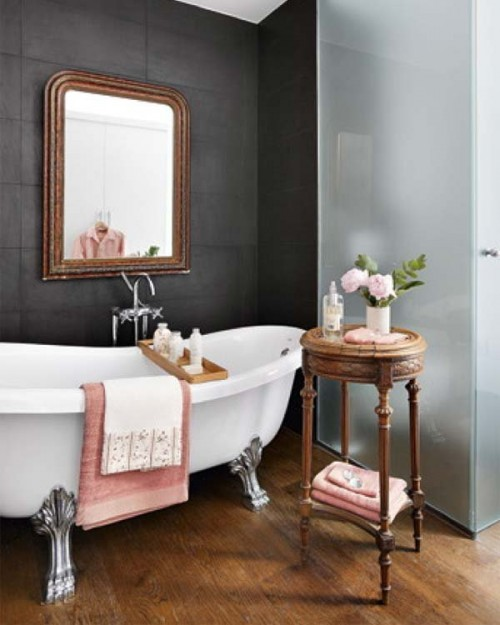 an eclectic bathroom with a dark statement wall, a vintage tub, an ornate mirror and a frosted glass shower