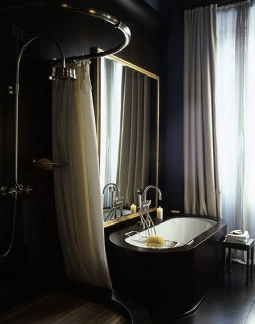 a contemporary dark bathroom with black walls, a black stone clad tub, a gold frame mirror and curtains for the shower space