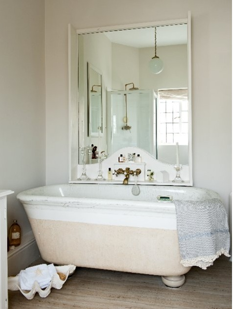 a retro coastal bathroom in neutrals, with a large tub, a statement mirror with a shelf and a large shell for storage