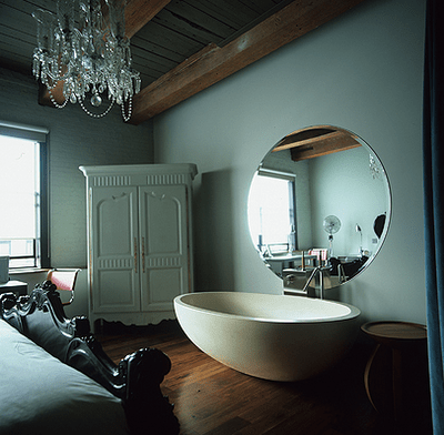 a vintage bedroom with a crystal chandelier, a large oval tub and a round mirror over it for an eclectic look