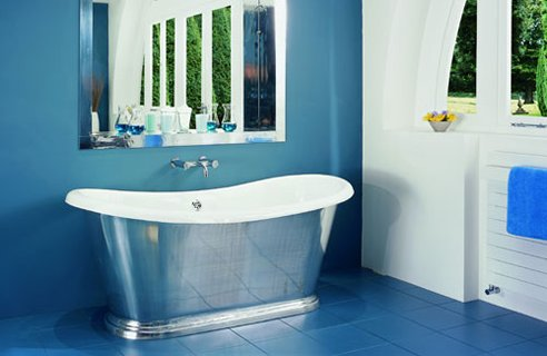a modern blue bathroom wtith a white wall, a metal clad bathtub and a large mirror over the tub