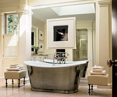 a refined vintage bathroom in neutrals, with a metal clad tub, upholstered ottomans and a mirror wall with an artwork