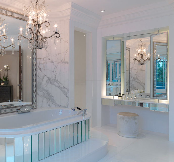 a luxurious bathroom in white marble, with a crystal chandelier, a mirror clad bathtub and a mirror over it for a statement