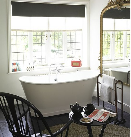 a retro bathroom with vintage black furniture,black shades, an oval tub and a large ornate mirror in front of the tub