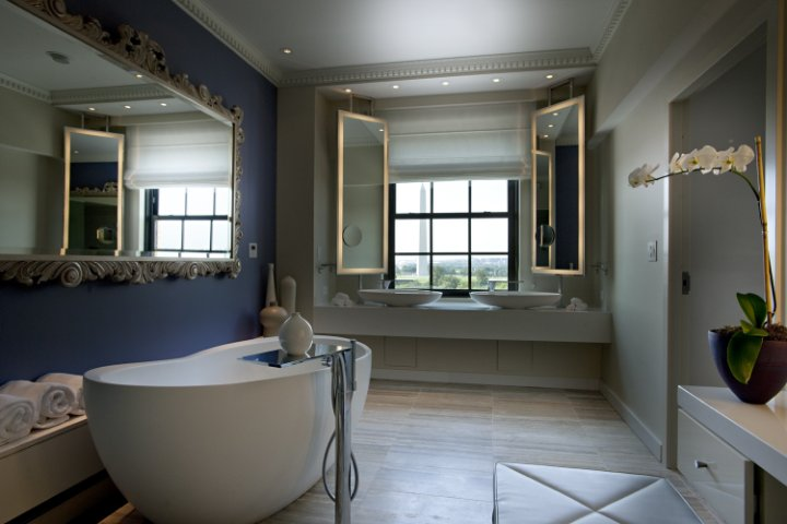 a refined contemporary bathroom with a statement blue wall, an ornate mirro over the modenr oval tub, lit up mirror at the sinks and potted orchids