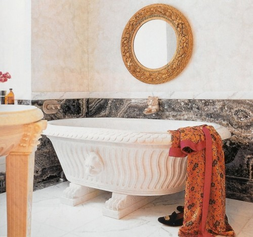 a quirky and refined bathroom done in marble and stone, with a bowl-like bathtub, an ornate mirror, a stone table