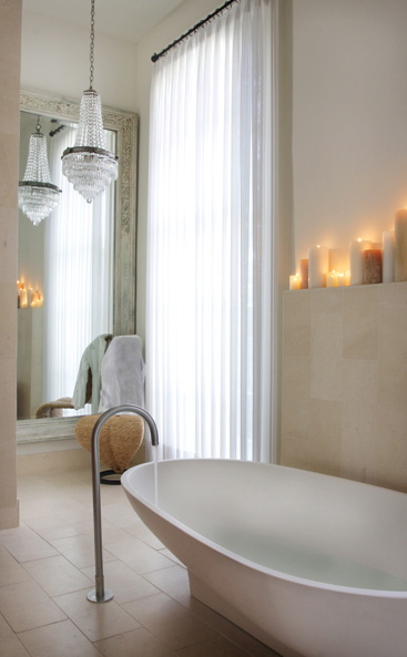 a contemporary bathroom in neutrals, a crystal chandelier, a mirror wall, an oval tub, pillar candles on the shelf over it
