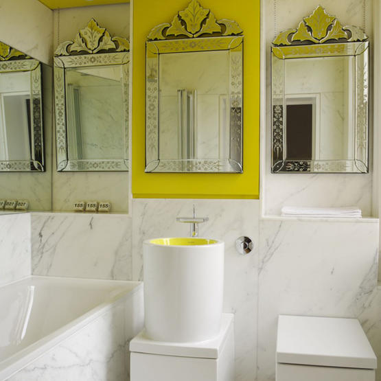 a contemporary bathroom done with white marble, several mirrors, a bathtub and a round sink all done in white marble