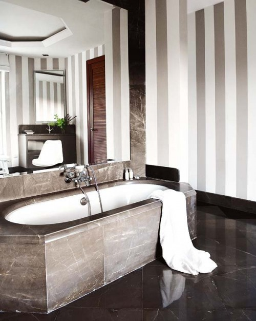a modern luxurious bathroom with striped walls, a dark floor, a stone bathtub and a whole mirror wall over it to enlarge the space