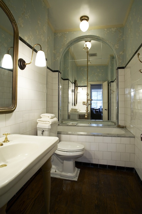 a retro bathroom with floral walls, white subway tiles, touches of gold and brass and a large arched mirror over the tub