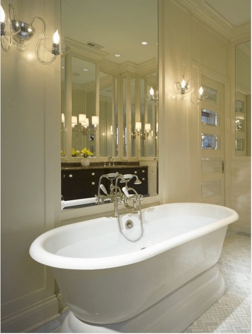 a neutral luxurious bathroom with retro touches, a retro tub, vintage fixtures and a mirror over the tub