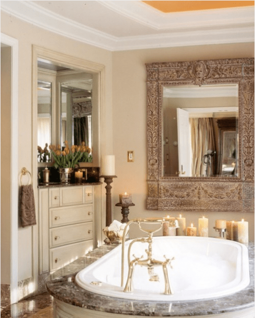 a refined bathroom with neutral furniture, a stone enclosed bathtub, pillar candles and a large ornate mirror over the tub