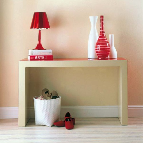 a narrow metallic console table and a white wicker cubby as a simple shoe storage in the entryway