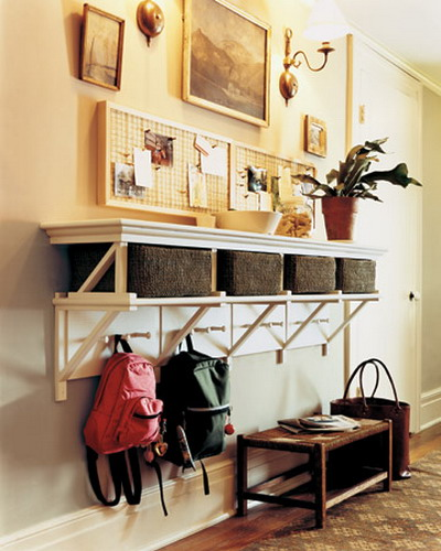 an open shelf and wicker cubbies for storage plus hooks make up a cool storage unit for a small entryway