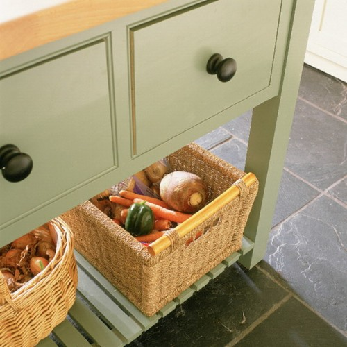a green kitchen island with an open storage space, a couple of baskets for storing vegetables and fruits with a rustic touch