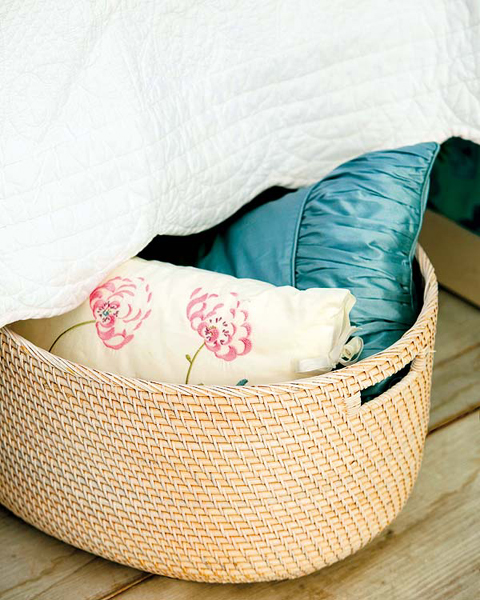 an oval basket inserted under a sofa or a bed will give you some storage space for blankets and pillows