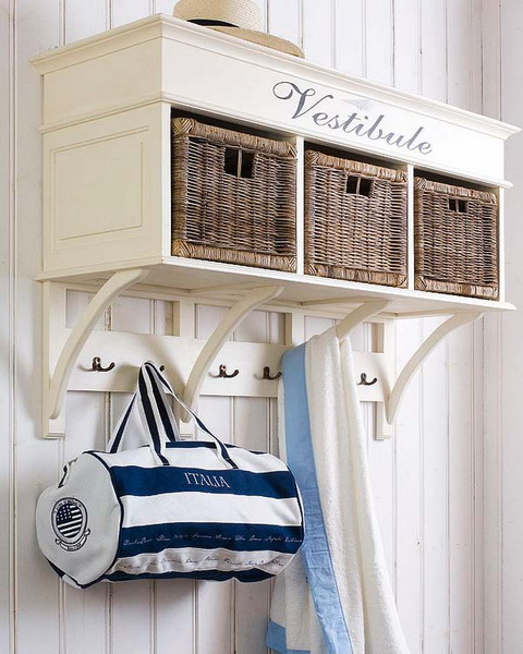 a white entryway storage unit with a shelf with inserted wicker cubbies for closed and hidden storage and some hooks for clothes