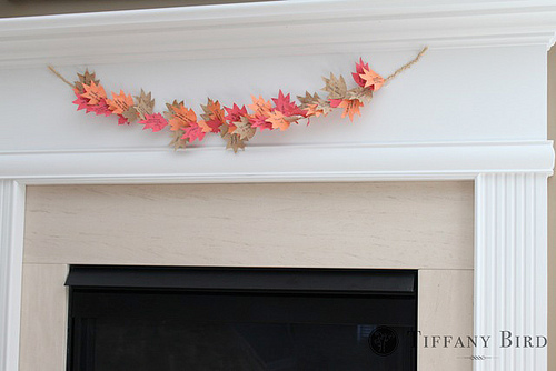 a bold paper leaf Thanksgiving garland hung over the fireplace is a stylish and bright decor idea to try
