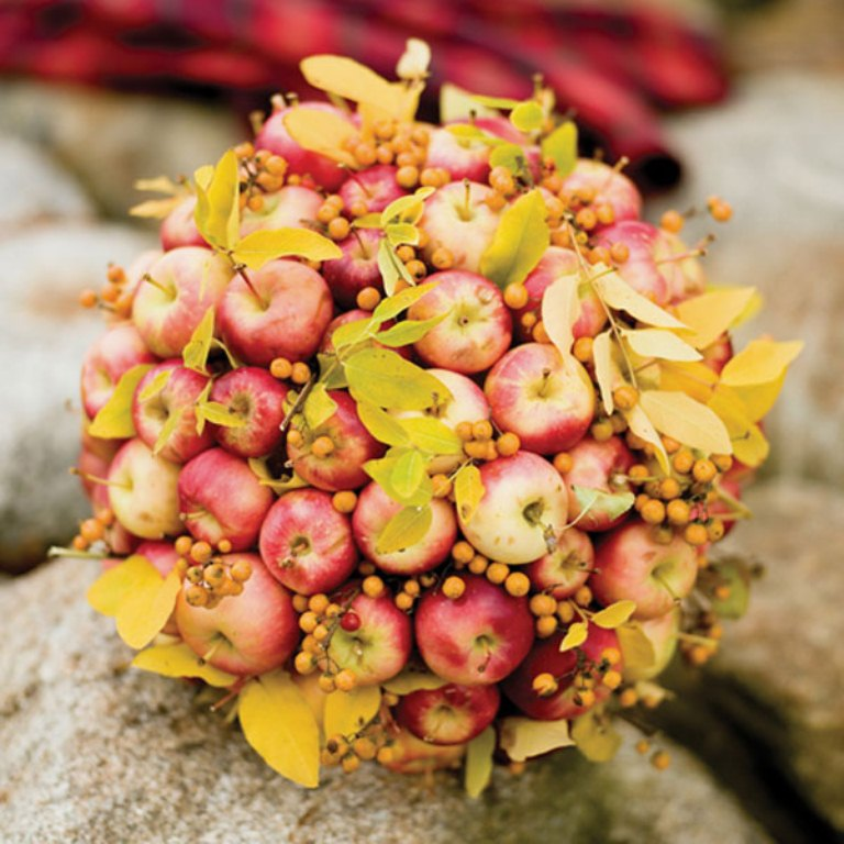 a fall centerpiece of fall apples, fall leaves and berries is a lovely decoration in bright shades