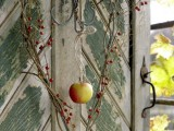 a creative vine heart-shaped wreath with berries and a fall apple in the center is great for outdoors and indoors
