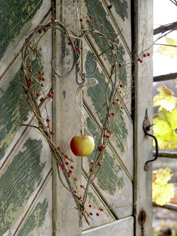 a creative vine heart shaped wreath with berries and a fall apple in the center is great for outdoors and indoors