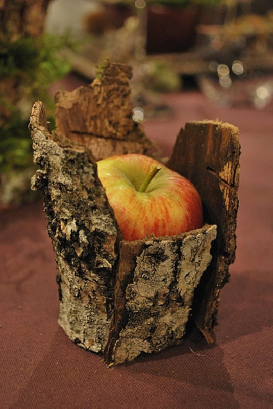 an apple placed into a tree stump is a nice woodland or rustic fall decoration to rock