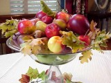 a glass bowl with pears, apples, fall leaves and acorns is a gorgeous fall centerpiece
