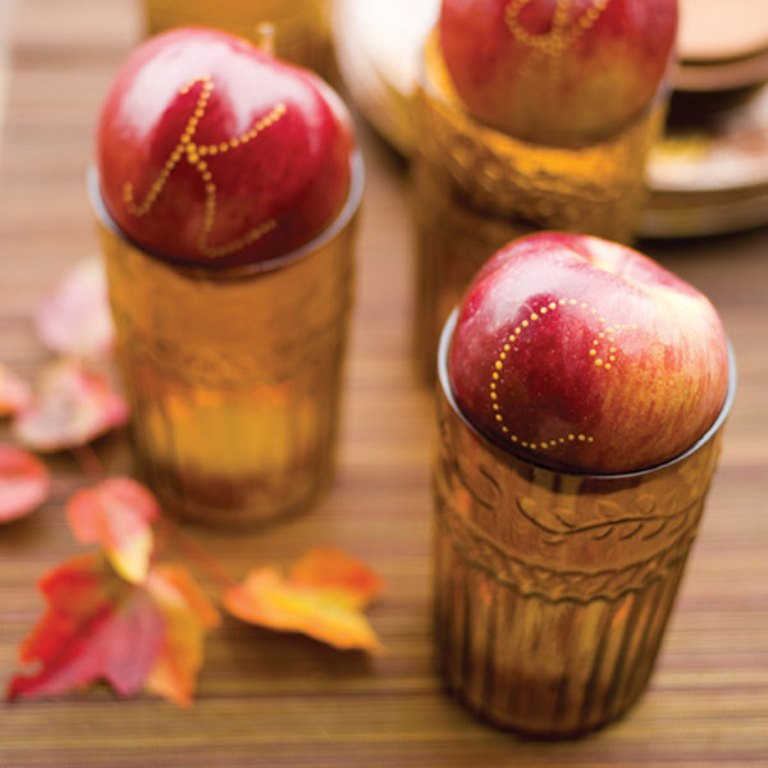 use letters on red apples placed on amber glasses as place cards that are yummy