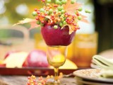 a red apple with fall leaves and berries placed on an amber glass is a cool fall decoration to try