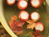 fall apples as candleholders cand be floating and you may add fall leaves to make the arrangement look cooler