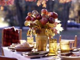 a cool and easy rustic fall centerpiece of a mustard vase with natural fall leaves and red apples is very yummy