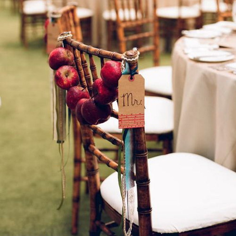 a red apple garland with ribbons and tags hung on a chair back is a cool decoration for a fall wedding or a party